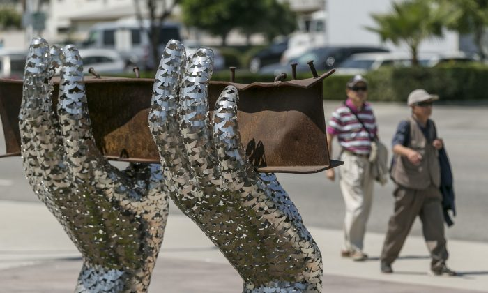 "Pedestrians walk by artist Heath Satow's sculpture ""Reflect,"" made with a damaged, rusted I-beam from the collapsed World Trade Center buildings, outside the Rosemead, Calif., city hall plaza, on Aug. 26, 2016. The 9/11 memorial sculpture has 2,976 interlocking birds representing individual victims from the 2001 attacks. (AP Photo/Damian Dovarganes)"