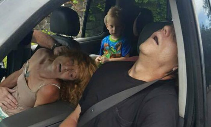 This Sept. 7, 2016 photo released by the East Liverpool Police Department, a young child sits in a vehicle behind his grandmother and a man, both of whom are unconscious from a drug overdose, in East Liverpool, Ohio. The police department said it's trying to show the impact of the heroin and painkiller epidemic by sharing photos of the boy sitting in the vehicle behind the slumped-over adults who were later revived with an overdose antidote. The couple faces child-endangering and other charges. (East Liverpool Police Department via AP)