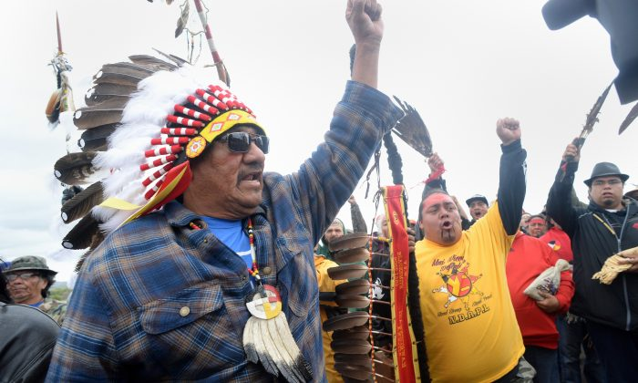 J.R. American Horse (L) raises his fist with others while leading a march to the Dakota Access Pipeline site in southern Morton County North Dakota. (Will Kincaid/The Bismarck Tribune via AP)