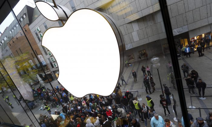 People wait in front of an Apple store in Munich, before the worldwide launch of the iPhone 6s on Sept. 25, 2015. (AP Photo/Matthias Schrader)