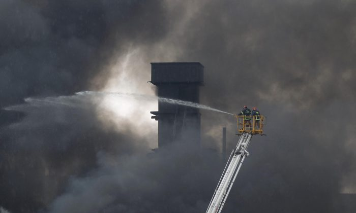 Firefighters on a ladder spray water to put out the fire at a packaging factory in Tongi industrial area outside Dhaka, Bangladesh, on Sept. 10, 2016. A boiler exploded and triggered a fire at a packaging factory near Bangladesh's capital. (AP Photo/A. M. Ahad)