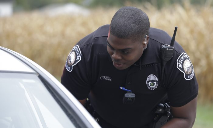 A body camera is attached to the uniform of Whitestown Police Department officer Reggie Thomas during a traffic stop, in Whitestown, Ind., on Sept. 29, 2015. (AP Photo/Darron Cummings)