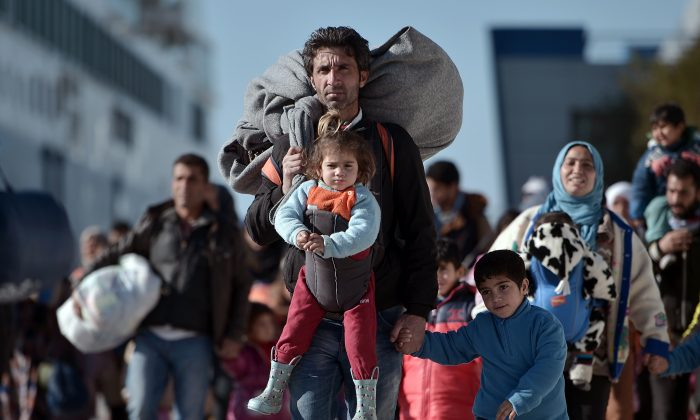 Thousands of migrants and refugees walk through the port of Piraeus after arriving from the Greek islands of Lesbos and Chios on Feb. 1, 2016. (Louisa Gouliamaki/AFP/Getty Images)