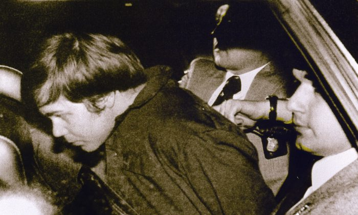 This March 30, 1981 file photo shows John Hinckley Jr. (L) escorted by police in Washington, D.C., following his arrest after shooting and seriously wounding then President Ronald Reagan. (AFP/AFP/Getty Images)