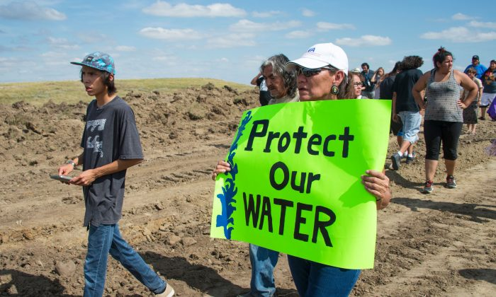 "A protester holds a sign reading ""Protect Our Water"" as Native Americans and their supporters walk on land designated for the Dakota Access Pipeline (DAPL), after protestors confronted contractors and private security guards working on the oil pipeline project, forcing them to retreat, near Cannon Ball, N.D., on Sept. 3, 2016. (Robyn Beck/AFP/Getty Images)"