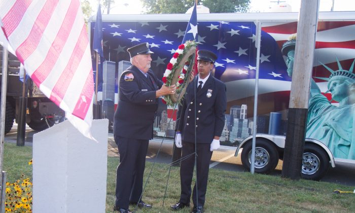 Former New York City Fire Department member and former Howells Fire Chief, Charles Gersbeck, lays a wreath with his son James Gersbeck, a fireman with the Howells Fire Department, by the 9/11 memorial in Veteran's Memorial Park in Wallkill on Sept. 11, 2016. The wreath-laying was part of the Town of Wallkill's remembrance ceremony for the 15th anniversary of the attacks on the World Trade Center and Pentagon. (Holly Kellum/Epoch Times)