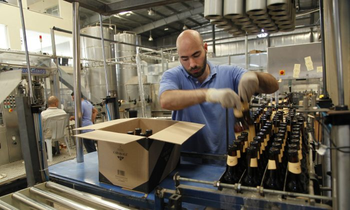 Carakale Brewery staffer Ramzi Kharoufeh fills a box with beer bottled, pasteurized and labeled that day in Fuheis, Jordan, on Sept. 6, 2016. (Sam McNeil/AP Photo)