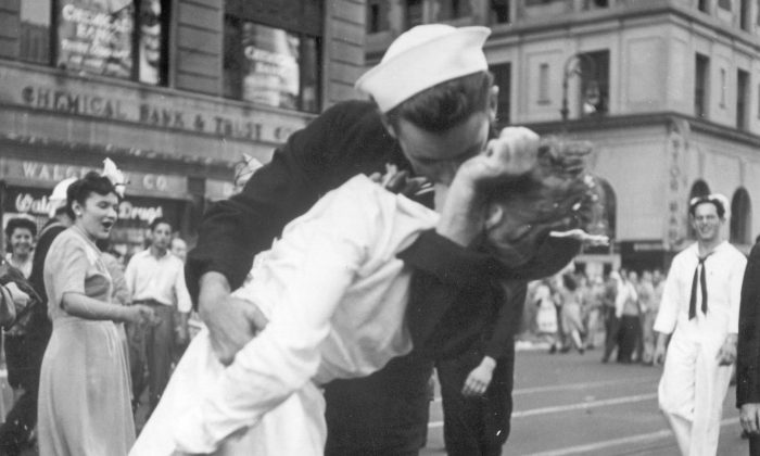 In this file photo a sailor and a nurse kiss passionately in Manhattan's Times Square, as New York City celebrates the end of World War II. (AP Photo/U.S. Navy/Victor Jorgensen)