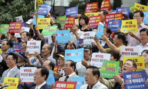 "South Korean shout slogans during a rally denouncing North Korea's latest nuclear test in Seoul, South Korea, Monday, Sept. 12, 2016. North Korea is capable of detonating another nuclear device anytime at one of its unused tunnels at the country's main atomic test site, Seoul official said Monday, three days after the country carried out its fifth bomb explosion. The letters read ""Overthrow Kim Jong Un and Discard North Korea's nuclear."" (AP Photo/Lee Jin-man)"