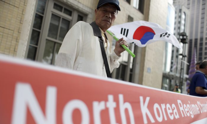 A South Korean protester holds a South Korean national flag before a rally denouncing North Korea's latest nuclear test, in Seoul, South Korea, Monday, Sept. 12, 2016. North Korea is capable of detonating another nuclear device anytime at one of its unused tunnels at the country's main atomic test site, Seoul official said Monday, three days after the country carried out its fifth bomb explosion. (AP Photo/Lee Jin-man)