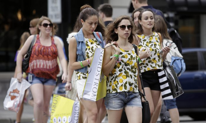 Shoppers walk along Michigan Avenue in Chicago on July 29, 2019. (Joshua Lott/Getty Images)