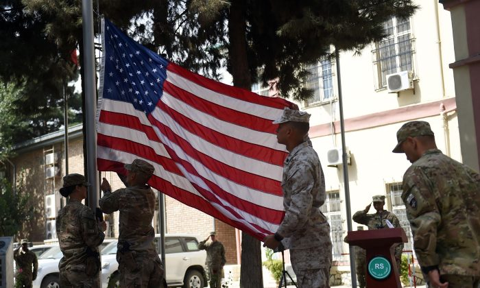 US military personnel lower the US flag at a memorial ceremony in honour of the 15th anniversary of the September 11, 2001 attacks on New York and Washington DC, at the International Security Assistance Force (ISAF) headquarters in Kabul on September 11, 2016.      (WAKIL KOHSAR/AFP/Getty Images)