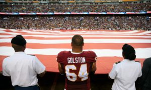 Redskins Players Join Armed Forces Members in Holding Flag During National Anthem