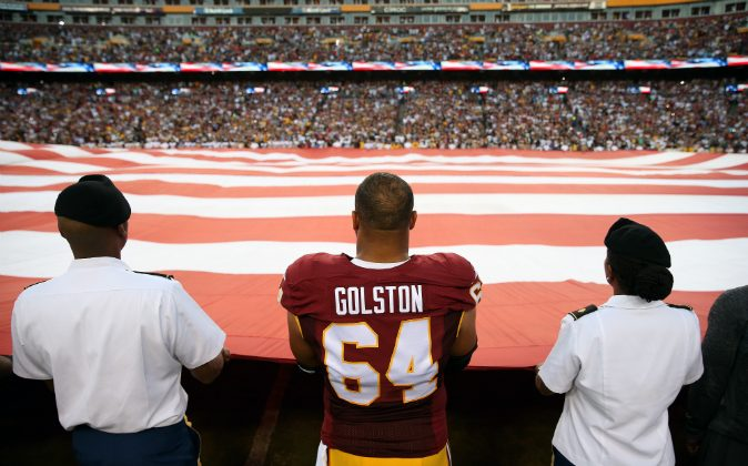 Defensive end Kedric Golston #64 of the Washington Redskins holds the American flag during the national anthem prior to a game against the Pittsburgh Steelers at FedExField on September 12, 2016 in Landover, Maryland. (Patrick Smith/Getty Images)