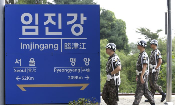 South Korean army soldiers walk by a signboard showing the distance to the North Korean capital Pyongyang and to South's capital Seoul from Imjingang Station near the border village of the Panmunjom in Paju on Sept. 11, 2016. (Ahn Young-joon/AP)