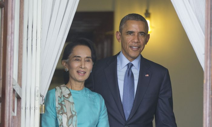 FILE - In this Nov. 14, 2014, file photo, U.S. President Barack Obama, right, walks out with Myanmar's Aung San Suu Kyi at her home before the start of their joint news conference in Yangon, Myanmar. Suu Kyi's latest visit to Washington signals her transformation from long-imprisoned heroine of Myanmar's democracy struggle to a national leader focused on economic growth. Obama will discuss rolling back more of the sanctions that were applied when the nation was under military rule, and Suu Kyi will be courting the American business community at a dinner where tables go for as much as $25,000. (AP Photo/Pablo Martinez Monsivais, File)