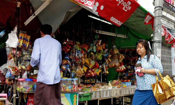 Pedestrian walks past while a man buy cigarette at a roadside shop Thursday, Sept. 15, 2016, in Yangon, Myanmar. Myanmar economists and businessmen welcome President Barack Obama's announcement that the U.S. will lift economic sanctions and restore long-lost trade benefits to the Southeast Asian country. (AP Photo/Thein Zaw)