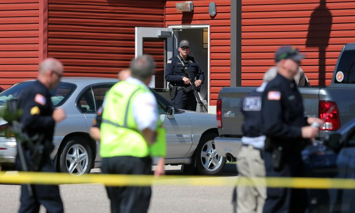 A Cheyenne Police officer guards an entrance to  Heritage Court Apartments Wednesday, Sept. 14, 2016 in northeast Cheyenne, Wyo.  A 77-year-old man living at a senior citizen apartment complex shot three people at the complex Wednesday, killing one of them, and then killed himself nearby as officers closed in on him, police said. (Blaine McCartney/The Wyoming Tribune Eagle via AP)