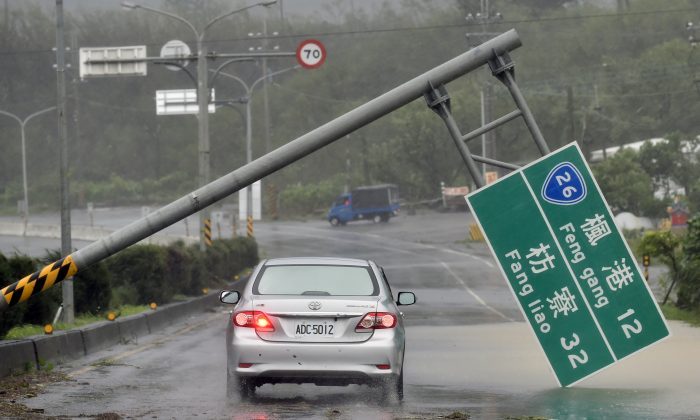 A car drives pass a collapsed traffic sign, toppled by strong winds of typhoon Meranti, as it pounded southern China and Taiwan on Sep. 14, 2016. Parts of the regions hit were brought to a standstill as the strongest typhoon of the year skirted past the island's southern tip, knocking out power and water supply for over a million households. (Sam Yeh/AFP/Getty Images)