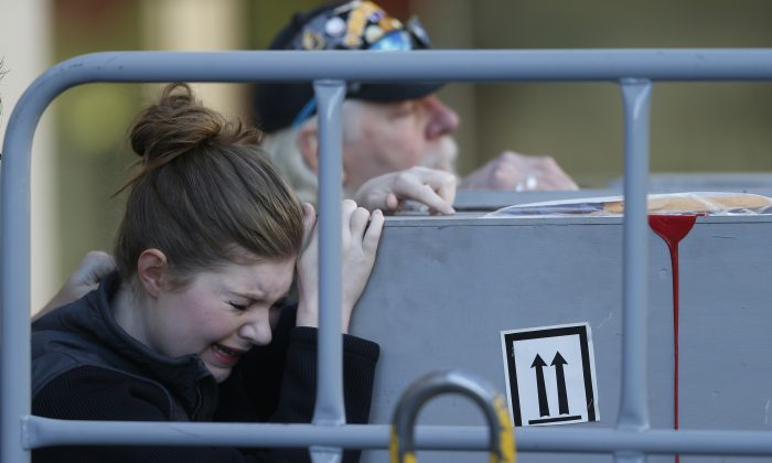 Katie Shirley of Arvada, Colo., joins her father, Russ, back, of Rapid City, S.D., in touching the casket bearing the body of her brother and his son, 24-year-old Levi Shirley, as the bodies of Shirley and Jordan MacTaggart were unloaded from an Amtrak train at Union Station early Friday, Sept. 16, 2016, in Denver. (AP Photo/David Zalubowski)