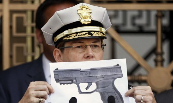 Columbus Police Chief Kim Jacobs holds up a photo showing the type of BB gun that police say a 13-year-old boy pulled from his waistband just before he was shot   (Fred Squillante/The Columbus Dispatch via AP)