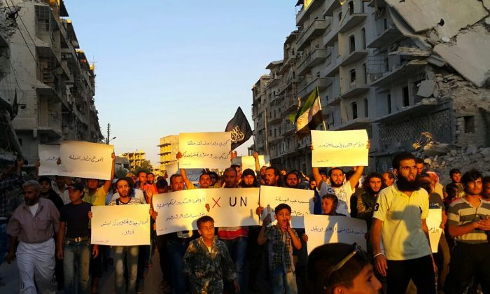 """Activists in Syria's besieged Aleppo protest against the United Nations for what they say is its failure to lift the siege off their rebel-held area, on Sept. 13, 2016. Dozens of protesters marched in al-Shaar neighborhood heading toward the Castello road, the area from which aid is expected to be delivered. """"Hunger better than humiliation,"""" one banner read. """"X the UN,"""" another read. (Modar Shekho via AP)"""