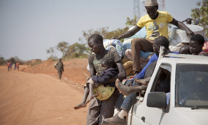 Refugees who fled the recent violence in South Sudan and crossed the border into Uganda arrive and await transportation from a transit center in the town of Koboko, Uganda, on Jan. 6 2014. (AP Photo/Rebecca Vassie)