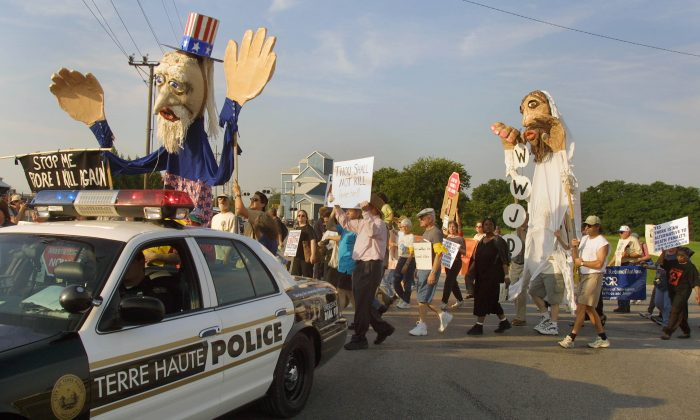 A Terre Haute police car precedes anti-death penalty demonstrators during a march along a street from St. Margaret Mary Parish in Terre Haute, Indiana, on June 10, 2001. (Tim Boyle/Getty Images)