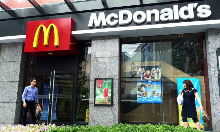 People walk by a McDonald's restaurant  on July 28, 2014 in Shanghai. McDonald's is finalizing a sale of the rights to run its Chinese restaurants. (Johannes Eisele/AFP/Getty Images)