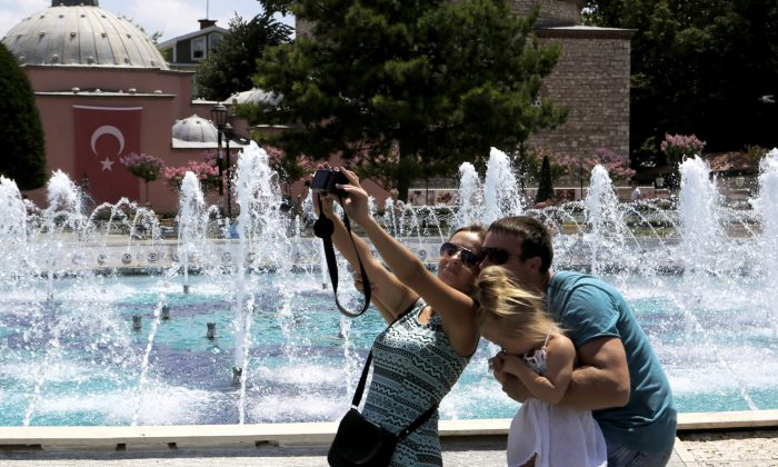 Tourists take a selfie at the Byzantine-era Hagia Sophia, in the historic Sultanahmet district of Istanbul on July 26, 2016. (AP Photo/Petros Karadjias)