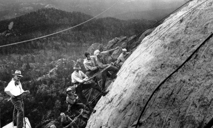 Sculptor Gutzon Borglum (L) directs drillers suspended by cables from the top of the mountain as they work on the head of President George Washington at the Mount Rushmore Memorial in the Black Hills area near Keystone, S.D., on July, 22, 1929. (AP Photo)