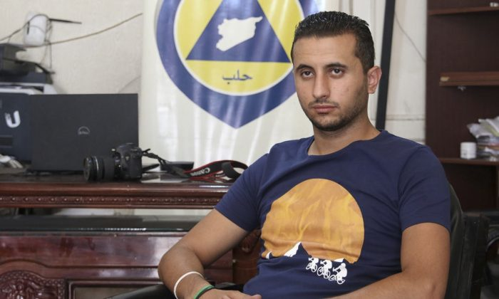 Ibrahim Alhaj, 26-year old member of Syrian Civil Defense, also known as White Helmets, sits in front of a banner for the first responders rescue group in Aleppo, Syria, in August 2016. (Handout from Ibrahim Alhaj via AP)