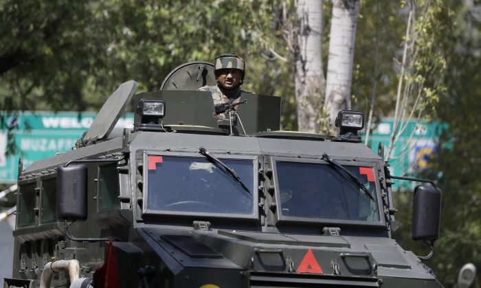 An Indian army soldier guards the army base which was attacked by suspected rebels in the town of Uri, west of Srinagar, Indian controlled Kashmir, on Sept. 18, 2016. (AP Photo/Mukhtar Khan)