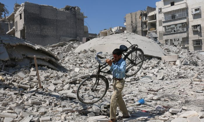 A Syrian man carrying a bicycle makes his way through the rubble of destroyed buildings following a reported airstrike on the rebel-held Salihin neighborhood of the northern city of Aleppo, on Sept. 11, 2016. (Ameer Alhalbi/AFP/Getty Images)