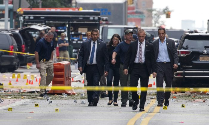New York Gov. Andrew Cuomo, right, walks from the scene of an explosion on West 23rd street in Manhattan's Chelsea neighborhood, in New York, Sept. 18, 2016, after an incident that injured passers-by Saturday night. (AP Photo/Craig Ruttle)