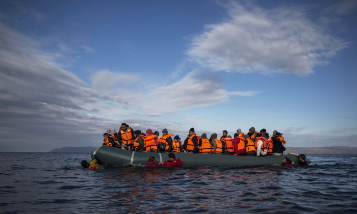 Refugees and migrants arrive on an inflatable vessel from the Turkish coast to the northeastern Greek island of Lesbos on Dec. 3, 2015.  (AP Photo/Santi Palacios)