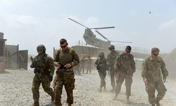 U.S. Army soldiers walk as a NATO helicopter flies overhead at coalition force Forward Operating Base (FOB) Connelly in the Khogyani District in eastern Afghanistan's Nangarhar Province on Aug. 13, 2015. (Wakil Kohsar/AFP/Getty Images)