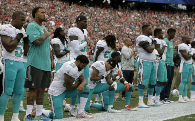 Miami Dolphins Arian Foster (29), Kenny Stills (10) and Michael Thomas (31) kneel during the national anthem before an NFL football game against the New England Patriots Sunday, Sept. 18, 2016, in Foxborough, Mass. (AP Photo/Steven Senne)