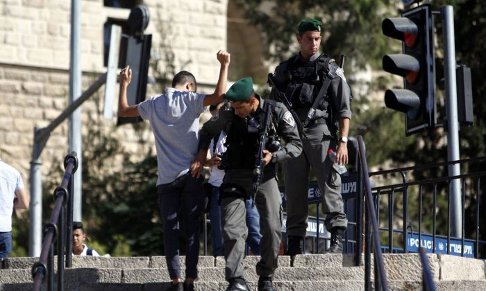 Israeli border police officers search a Palestinian man near the scene of a stabbing attack in Jerusalem's old city, Monday, Sept. 19, 2016. A Palestinian assailant stabbed two police officers outside Jerusalem's Old City early on Monday and was shot, police said, following a bloody weekend that shattered weeks of relative calm. (AP Photo/Mahmoud Illean)