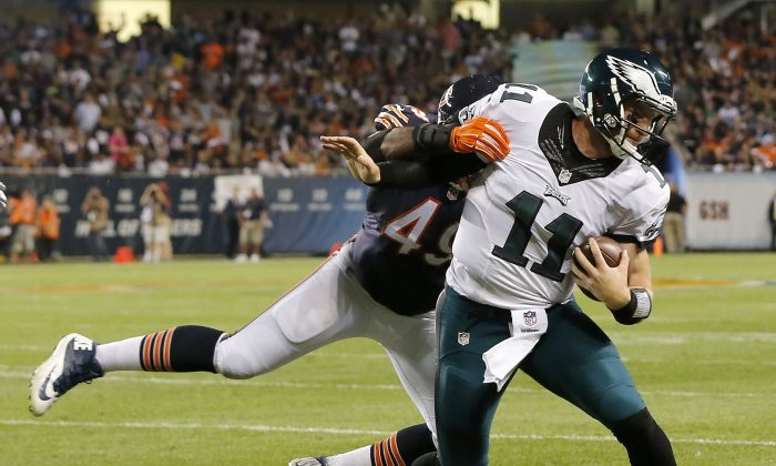 Philadelphia Eagles quarterback Carson Wentz (11) runs against Chicago Bears outside linebacker Sam Acho (49) during the first half of an NFL football game in Chicago on Sept. 19, 2016. (AP Photo/Charles Rex Arbogast)