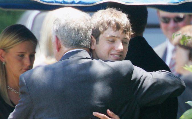In this June 29, 2006, file photo, John Ramsey hugs his son, Burke, facing camera, at the graves of his wife, Patsy, and daughter JonBenet, during services for his wife at the St. James Episcopal Cemetery in Marietta, Ga. Burke Ramsey filed a $150 million lawsuit against Werner Spitz after he claimed Ramsey killed his sister, Jon Benet on Oct. 7. (AP Photo/Ric Feld, File)