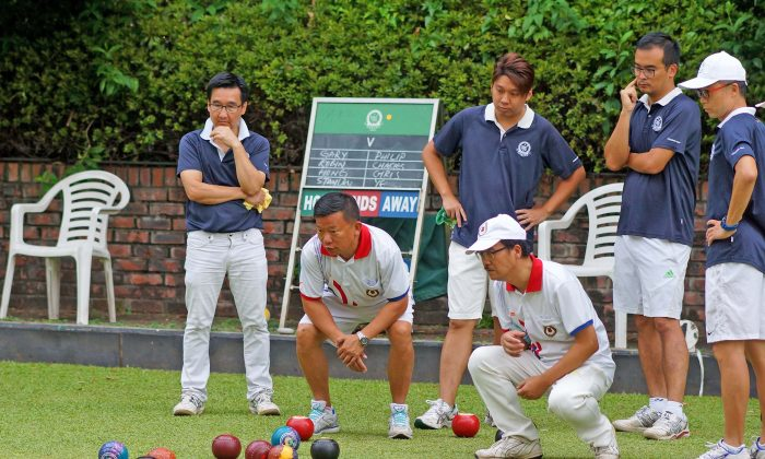 A tense moment for (L to R) back row Gary Pun, Lui Chi Hong, Robin Chok and Skip Stanley Lai of CCC-A as KBGC-A Philip Chan and Chris Chiu watch their Skip, Ye Sui Ying's last wood draw close to the jack to take 5 shots on the 17th end. However, Lai's team took 2 shots on the last end to win 20/15 with an overall score of 8/0 to CCC-A, and top position on the league table. KBGC-A lie second with 2 games in hand. (Mike Worth)