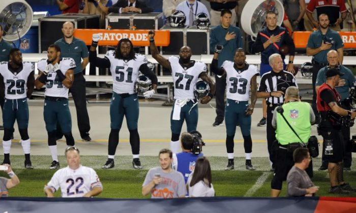 Philadelphia Eagles defensive end Steven Means (51), strong safety Malcolm Jenkins (27) and defensive back Ron Brooks (33) raise their arms during the national anthem before an NFL football game against the Chicago Bears, Monday, Sept. 19, 2016, in Chicago. (AP Photo/Kiichiro Sato)