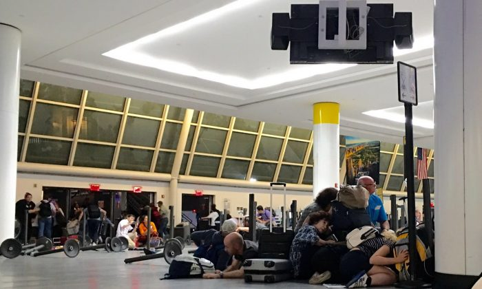 Passengers take cover while police looking for an active shooter at JFK International airport in New York on Aug. 14, 2016. (BRIGITTE DUSSEAU/AFP/Getty Images)