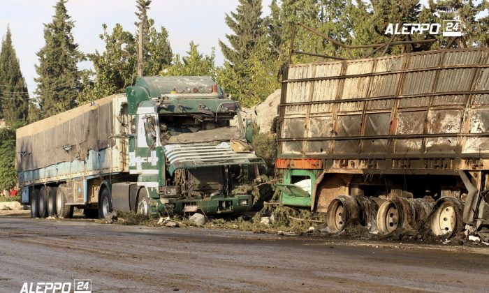 This image provided by the Syrian anti-government group Aleppo 24 news, shows damaged trucks carrying aid, in Aleppo, Syria, Tuesday, Sept. 20, 2016. A U.N. humanitarian aid convoy in Syria was hit by airstrikes Monday as the Syrian military declared that a U.S.-Russian brokered cease-fire had failed, and U.N. officials reported many dead and seriously wounded. (Aleppo 24 news via AP)
