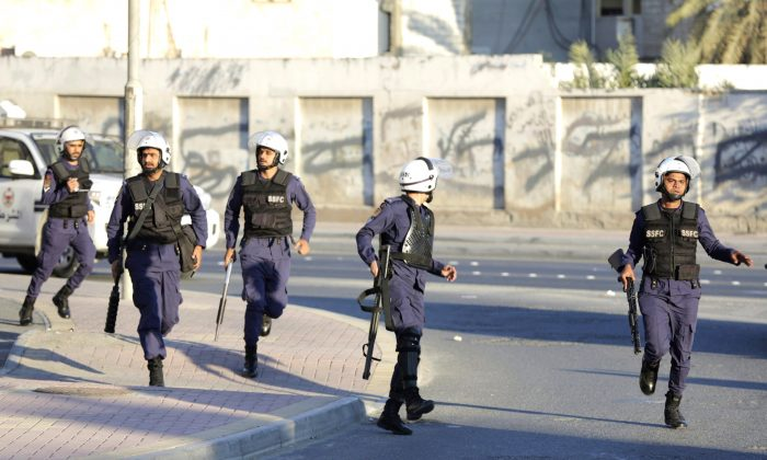 Riot police run toward protesters to disperse an anti-government march in Daih, Bahrain, on Feb. 13, 2016, in the run-up to the fifth anniversary of Bahrain's Arab Spring uprising. Researchers say a Canadian company is helping block news and opposition websites in Bahrain. (AP Photo/Hasan Jamali)