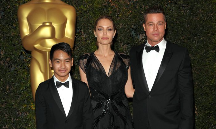 (L-R) Maddox Jolie-Pitt, Angelina Jolie and Brad Pitt attend the 2013 Governors Awards in Los Angeles. The FBI could possibly launch an investigation into child abuse allegations against Pitt. (John Shearer/Invision/AP, File)