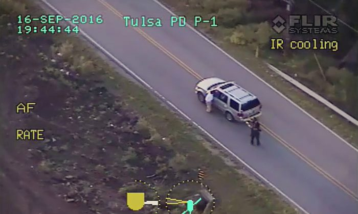 In this photo made from a Sept. 16, 2016 police video, Terence Crutcher (L) lowers his right arm as he is pursued by police officers moments before he was shot and killed by one of the officers in Tulsa, Okla.  (Tulsa Police Department via AP)