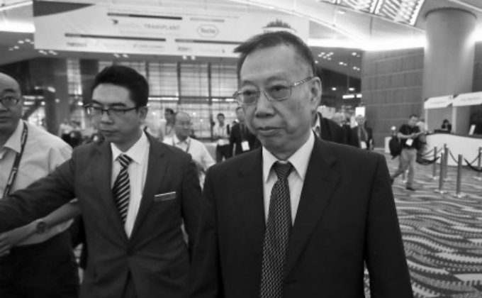 Huang Jiefu, the spokesperson on Chinese transplantation issues, dodges reporters at The Transplantation Society's recent biennial conference in Hong Kong on Aug. 19. (Yu Kong/Epoch Times)