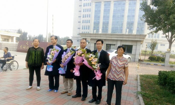 (2nd L-2nd R) Chinese human rights lawyers Zhang Zanning, Chang Boyang, Yu Wensheng, and Zhang Keke pose with the mothers of Falun Gong practitioners Zhou Xiangyang and Li Shanshan outside Tianjin Dongli People's Court in China on Sept. 13, 2016. (Epoch Times)